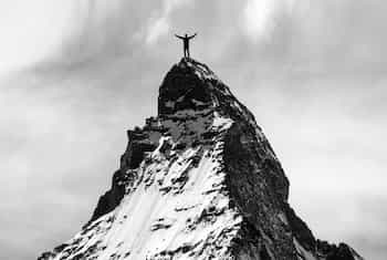 Man standing on the peak of a mountain